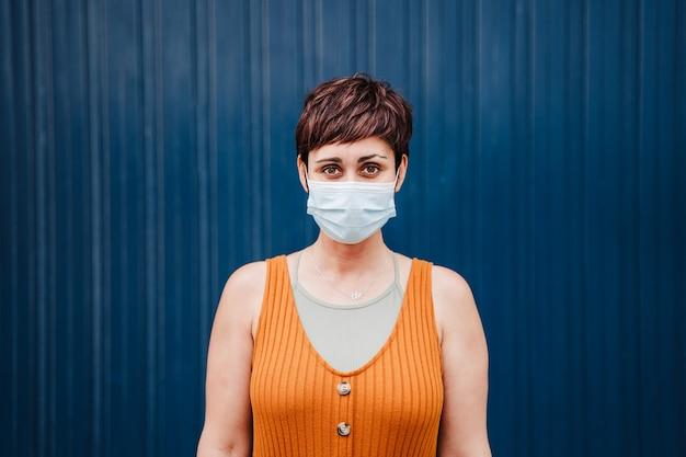 Mulher caucasiana ao ar livre usando máscara facial. pandemia durante o conceito de distância social do vírus corona.