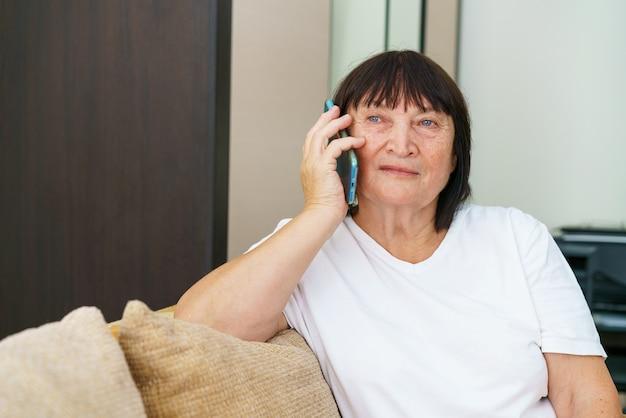 Mulher caucasiana aposentada alegre em roupas casuais está relaxando em casa, tendo uma conversa agradável ao telefone.