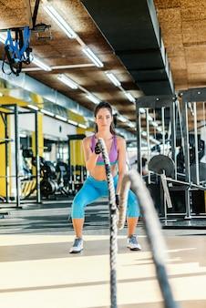 Mulher caucasiana apta com rabo de cavalo vestida com roupas esportivas, fazendo exercícios com cordas de luta. interior do ginásio.