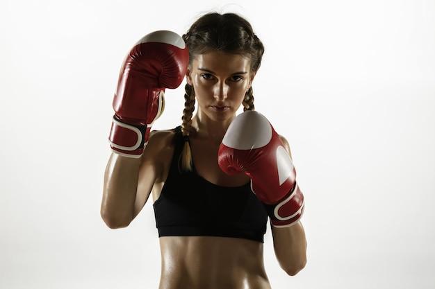 Mulher caucasiana apta em roupas esportivas de boxe isolado no fundo branco