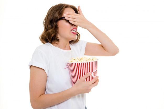 Mulher caucasiana assustada segurando o filme de relógio de pipocas.