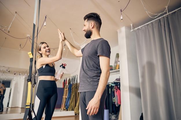 Mulher caucasiana atlética alegre cumprimentando seu instrutor de fitness com um high five em uma academia