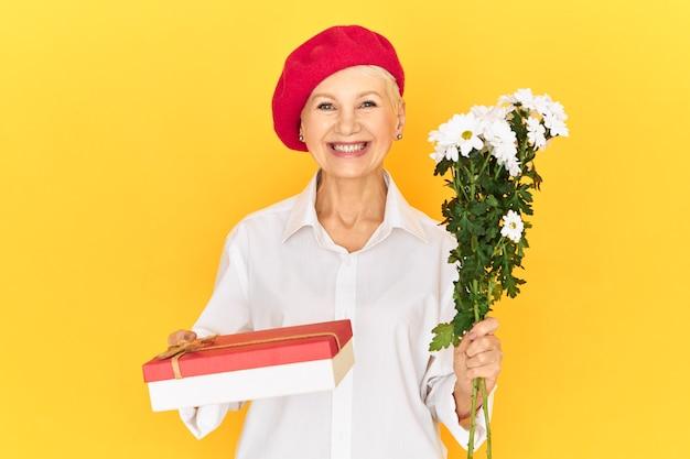 Mulher caucasiana atraente, alegre, com chapéus elegantes, olhando para a câmera com um sorriso largo e radiante, parabenizando você no dia internacional da mulher, dando-lhe um presente em caixa e flores brancas