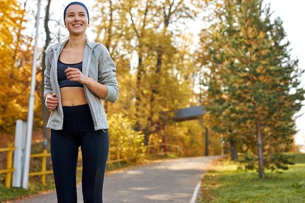 Mulher caucasiana atraente correndo no parque, praticando esportes