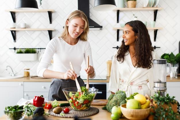 Mulher caucasiana atraente é cozinhar salada saudável e mulata bonita está olhando nela vestida de camisola de seda na cozinha projetada moderna