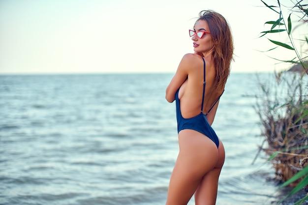 Mulher caucasiana atraente em maiô de biquíni, passeia na praia ao nascer do sol, apreciando o som de ...