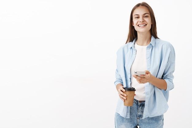 Mulher caucasiana atraente feliz satisfeita com uma blusa azul sobre uma camiseta segurando o copo de papel de café e o celular sorrindo com prazer feliz por ter uma pausa enquanto trabalhava no escritório