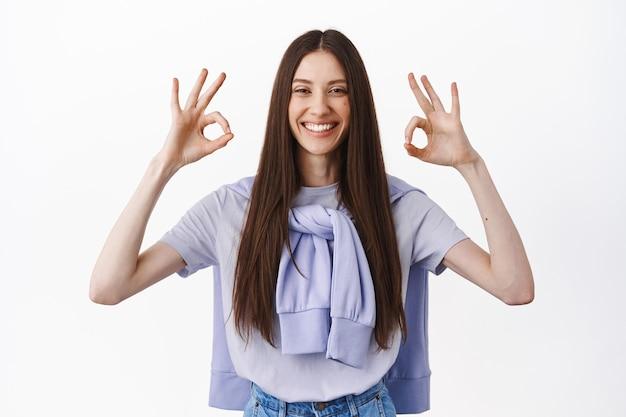Mulher caucasiana atraente mostrando gesto de ok ok, aceno e concordo, dar uma resposta positiva, elogiar a escolha perfeita, fazer um elogio, em pé sobre uma parede branca