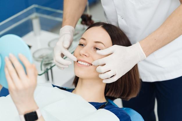 Mulher caucasiana atraente olhando seu lindo sorriso no espelho após tratamento estomatológico