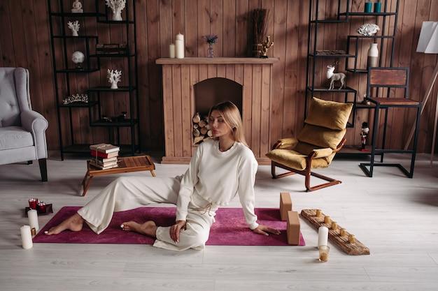 Mulher caucasiana bonita e relaxada com cabelo loiro em roupas brancas deitada no tapete de ioga com os olhos fechados