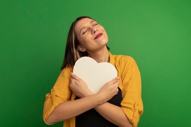 Mulher caucasiana bonita e satisfeita abraçando formato de coração no verde