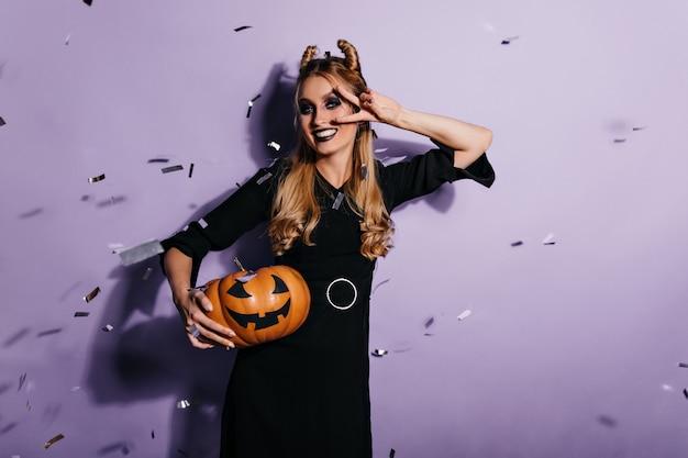 Mulher caucasiana bonita em vestido preto, posando após o baile de máscaras de halloween. foto interna de uma menina alegre sorridente com abóbora.