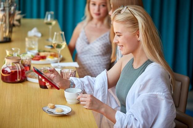 Mulher caucasiana bonita sentada em um café com um smartphone