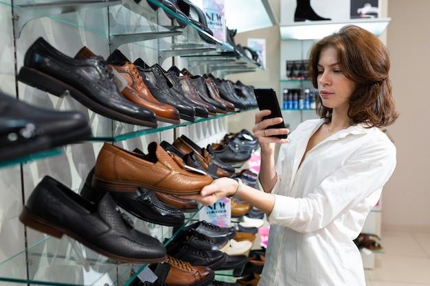 Mulher caucasiana branca tira foto de sapatos de couro de alta qualidade no departamento de sapatos masculinos.