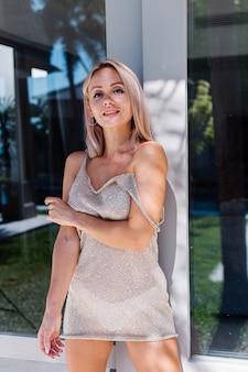 Mulher caucasiana, bronzeada e em forma, em um vestido curto brilhante do lado de fora da villa sob a luz natural