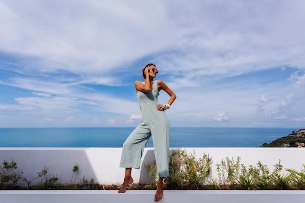 Mulher caucasiana bronzeada em forma de macacão azul claro na varanda de uma villa de luxo com vista para o mar tropical