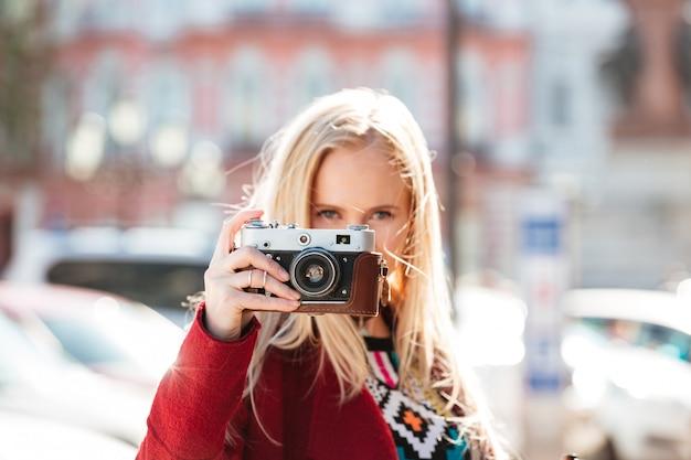 Mulher caucasiana, caminhando ao ar livre. segurando a câmera nas mãos.