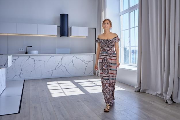 Mulher caucasiana caminhando pelo apartamento com vestido longo de verão
