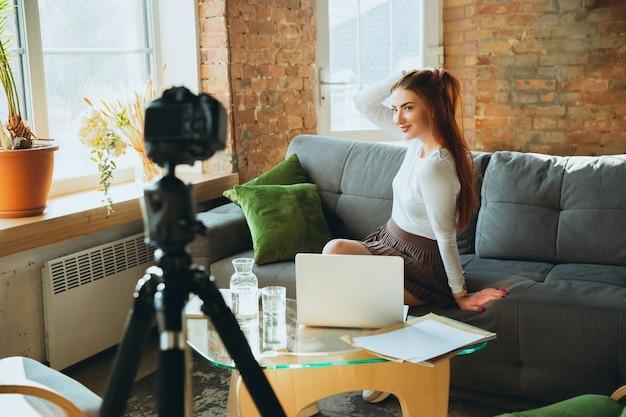 Mulher caucasiana, cantando durante o show online em casa isolada e em quarentena. usando câmera, laptop, streaming, cursos de gravação, dança. conceito de arte, suporte, música, hobby, educação.
