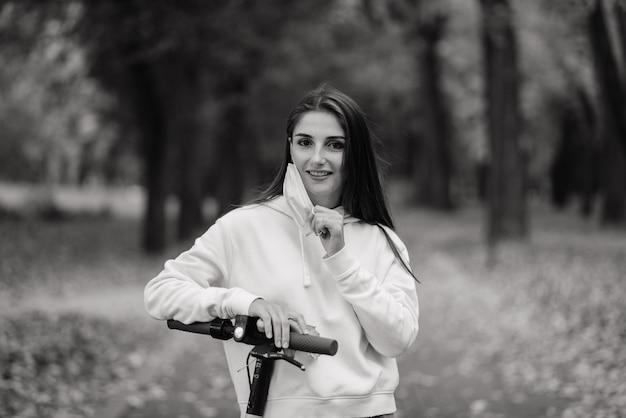 Mulher caucasiana casual usando máscara protetora montando scooter elétrica urbana no parque da cidade durante a pandemia cobiçada. conceito de mobilidade urbana.