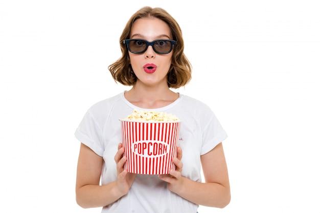 Mulher caucasiana chocada segurando pipocas usando óculos 3d