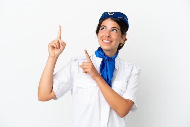 Mulher caucasiana com aeromoça de avião isolada no fundo branco apontando com o dedo indicador uma ótima ideia