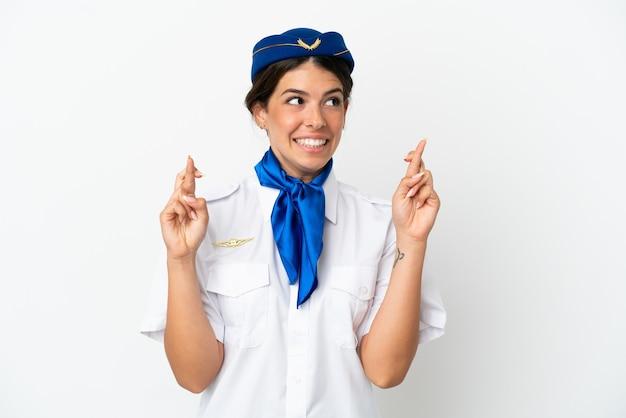 Mulher caucasiana com aeromoça de avião isolada no fundo branco com os dedos se cruzando