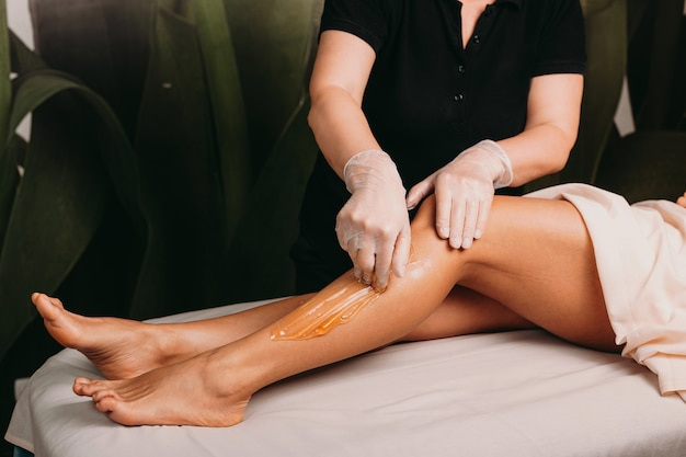 Mulher caucasiana com belas pernas fazendo uma depilação com açúcar durante um procedimento de spa profissional