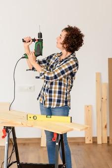 Mulher caucasiana com cabelo encaracolado tem uma furadeira nas mãos, pronta para fazer melhorias em casa.