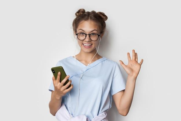 Mulher caucasiana com cabelo loiro sorrindo enquanto ouve música em uma parede branca usando fones de ouvido e telefone