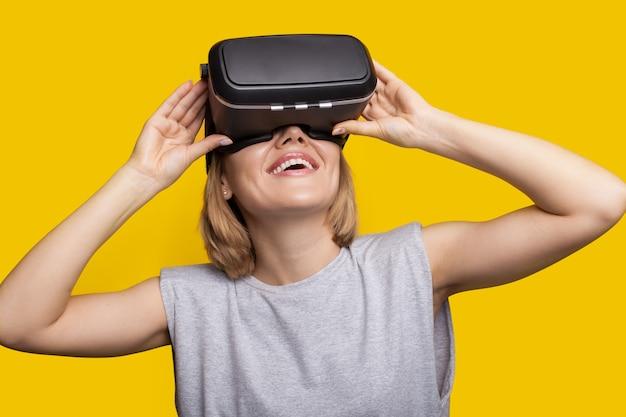 Mulher caucasiana com cabelo loiro sorrindo enquanto testa um novo fone de ouvido de realidade virtual em uma parede amarela