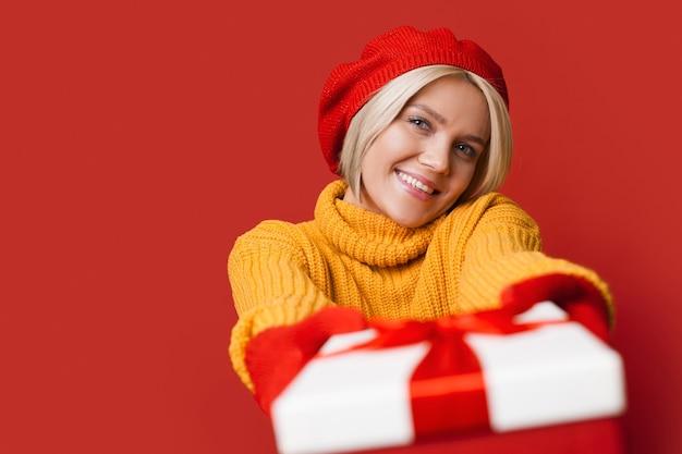 Mulher caucasiana com cabelo loiro, usando um lindo chapéu dando para a câmera uma caixa de presente sorrindo e anunciando algo na parede vermelha do estúdio