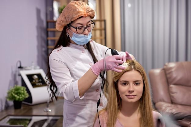 Mulher caucasiana com cabelo ralo no exame do couro cabeludo e cabelo com um microscópio, fazendo exame de tricologia. cosmetologista e cliente em gabinete moderno