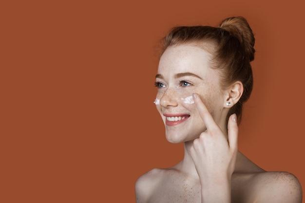 Mulher caucasiana com cabelo ruivo e sardas aplicando creme anti-envelhecimento nas bochechas sorrindo em uma parede vermelha com espaço livre
