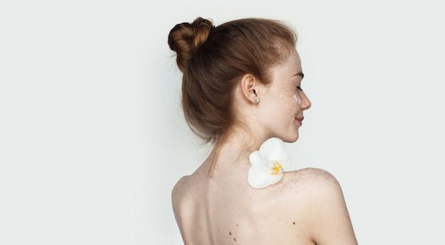 Mulher caucasiana com cabelo ruivo e sardas segurando uma flor nos ombros nus, aplicando creme no rosto, na parede branca do estúdio