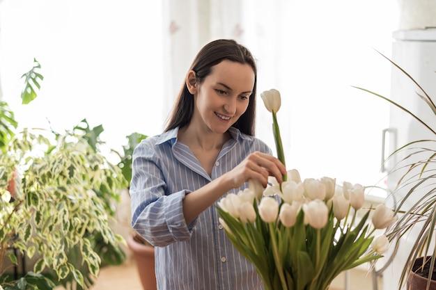 Mulher caucasiana com camisa azul cuidando de tulipas brancas em um vaso, ambientes inspirados pela natureza, primavera, conceito de casa aconchegante e confortável