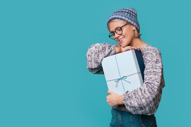 Mulher caucasiana com chapéu e óculos abraçando um presente sorrindo em uma parede azul com espaço livre