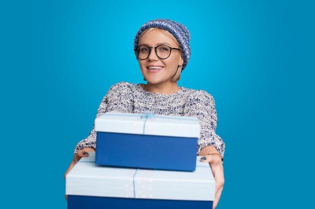 Mulher caucasiana com chapéu e óculos dando alguns presentes