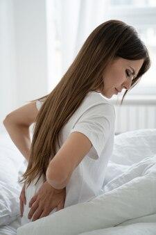 Mulher caucasiana com dores musculares nas costas