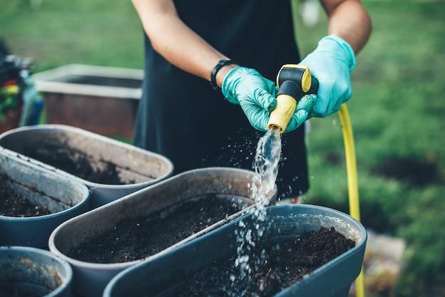 Mulher caucasiana com luvas rega os vasos com sementes enquanto trabalha no quintal