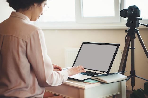 Mulher caucasiana com óculos, trabalhando no laptop, sentada na frente de uma câmera durante uma videochamada