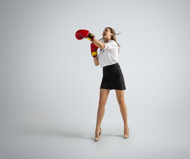 Mulher caucasiana com roupa de escritório boxe isolado na parede cinza