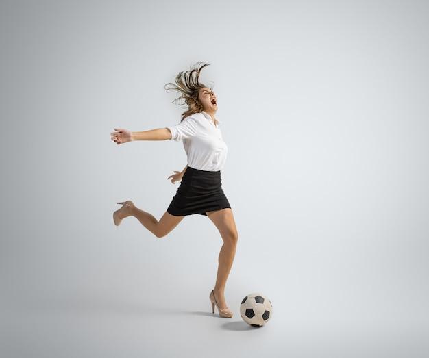 Mulher caucasiana com roupa de escritório chutando bola no cinza