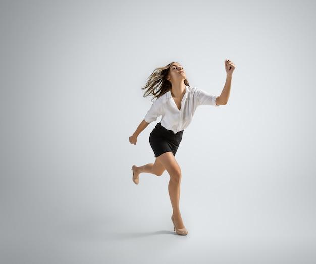 Mulher caucasiana com roupa de escritório correndo isolada na parede cinza