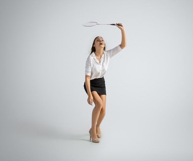 Mulher caucasiana com roupa de escritório joga badminton em cinza