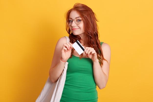 Mulher caucasiana com sacola de compras e cartão de crédito, olhando sorrindo diretamente para a câmera, mulher de cabelos vermelhos contra a parede amarela, indo às compras no shopping.