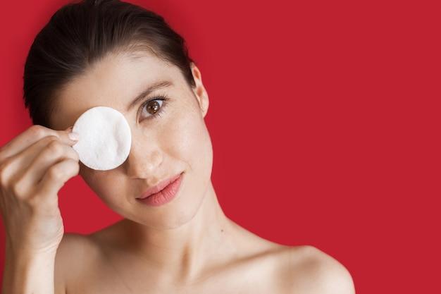 Mulher caucasiana com sardas cobrindo os olhos com um disco de algodão posando com os ombros nus em uma parede vermelha com espaço livre
