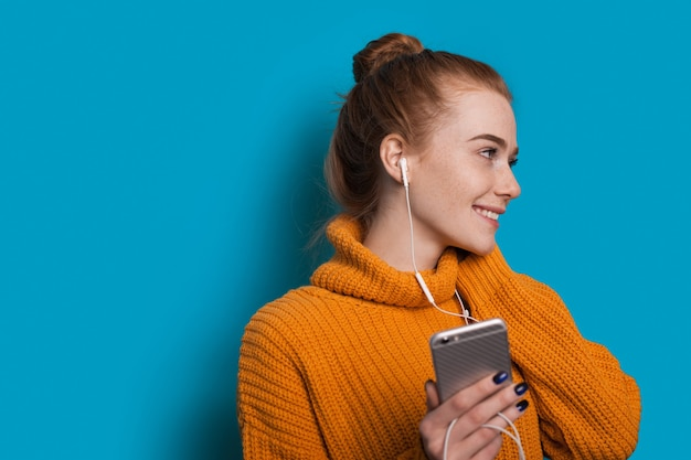 Mulher caucasiana com sardas e cabelo ruivo sorrindo enquanto olha para algum lugar e segurando seu celular com fones de ouvido em uma parede azul com espaço livre