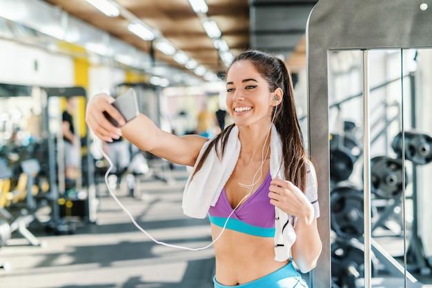 Mulher caucasiana com toalha no pescoço e fones de ouvido nas orelhas, sorrindo e tomando selfie em pé em uma academia.