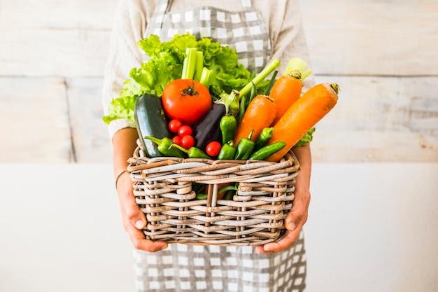 Mulher caucasiana com um balde cheio de alimentos saudáveis frescos coloridos e mistos, como frutas e vegetais